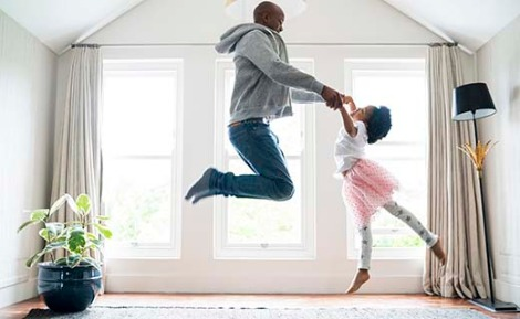 Father and daughter dancing in the living room