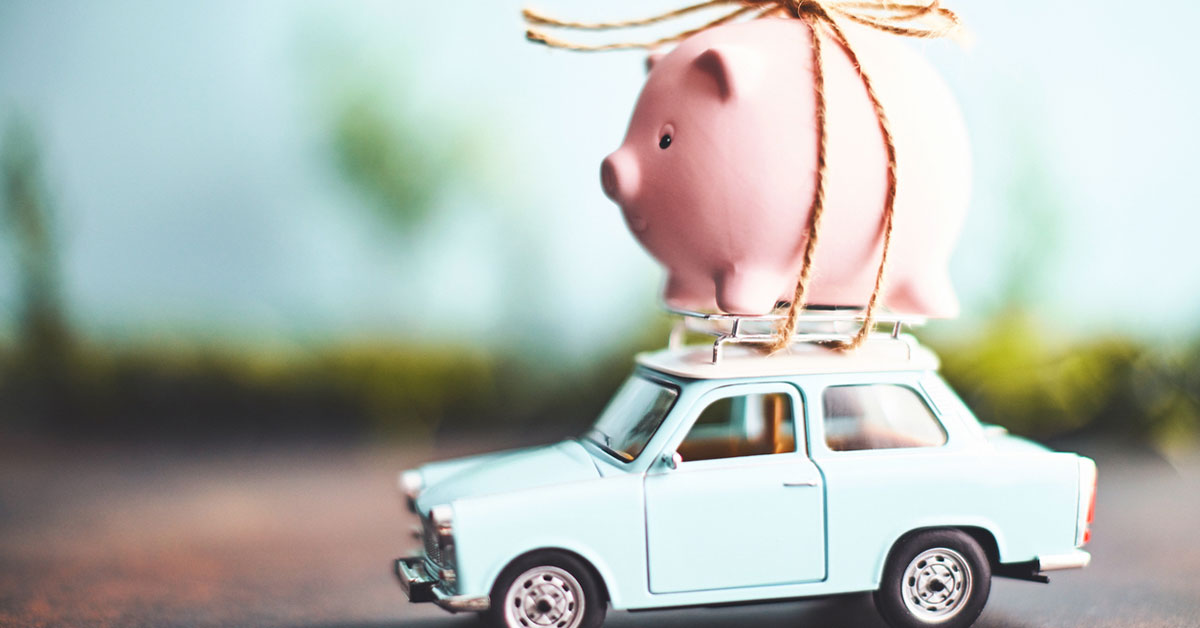 Little pink piggy bank tied to the top of an old toy car