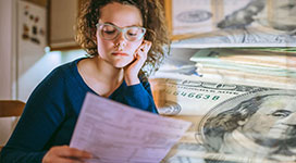 Young woman is looking at bills, feeling worried. Tax paying, bills, utilities concepts.