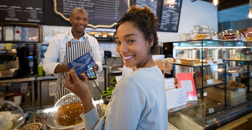 Woman holding debit card at bakery counter.