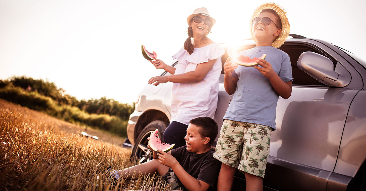 image of a mom and two children eating watermelon and laughing outside of their car